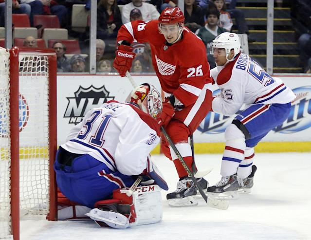 Detroit Red Wings' Tomas Jurco (26), of Slovakia, has his shot stopped by Montreal Canadiens goalie Carey Price (31) as teammate Francis Bouillon (55) helps defend the goal during the first period of an NHL hockey game Thursday, March 27, 2014, in Detroit. (AP Photo/Duane Burleson)