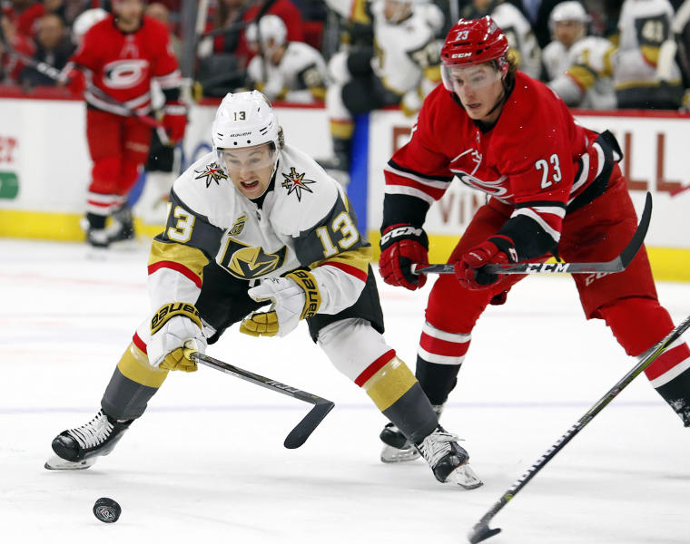 Golden Knights' Brendan Leipsic (13) and Carolina Hurricanes' Brock McGinn (23) eye the puck during the first period of an NHL hockey game, Sunday, Jan. 21, 2018, in Raleigh, N.C. (AP Photo/Karl B DeBlaker)