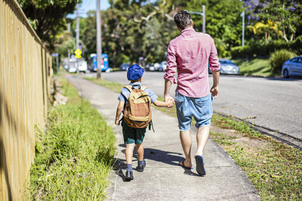 Rear view of an Australian aboriginal father taking his son to school, they are walking in the street holding hands.
