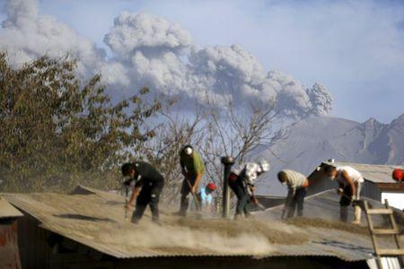 People clean an ash-covered roof of a house in Ensenada town, April 24, 2015. REUTERS/Ivan Alvarado