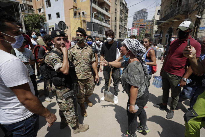 """A woman yells at Lebanese soldiers as French President Emmanuel Macron visits the Gemmayzeh neighborhood, which suffered extensive damage from the Tuesday explosion at the seaport, in Beirut, Lebanon, Thursday, Aug. 6, 2020. Lebanese officials targeted in the investigation of the massive blast that tore through Beirut sought to shift blame for the presence of explosives at the city's port, and the visiting French president warned that without serious reforms the country would """"continue to sink."""" (AP Photo/Hassan Ammar)"""