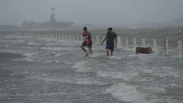 PHOTO: Two men walk on a flooded road as Hurricane Hanna makes landfall, Saturday, July 25, 2020, in Corpus Christi, Texas. (Eric Gay/AP)