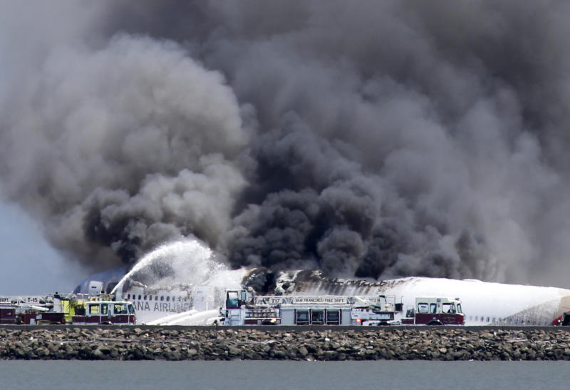 Fire crews work the crash site of Asiana Flight 214 at San Francisco International Airport in San Francisco, Saturday, July 6, 2013. (AP Photo/Bay Area News Group, John Green)