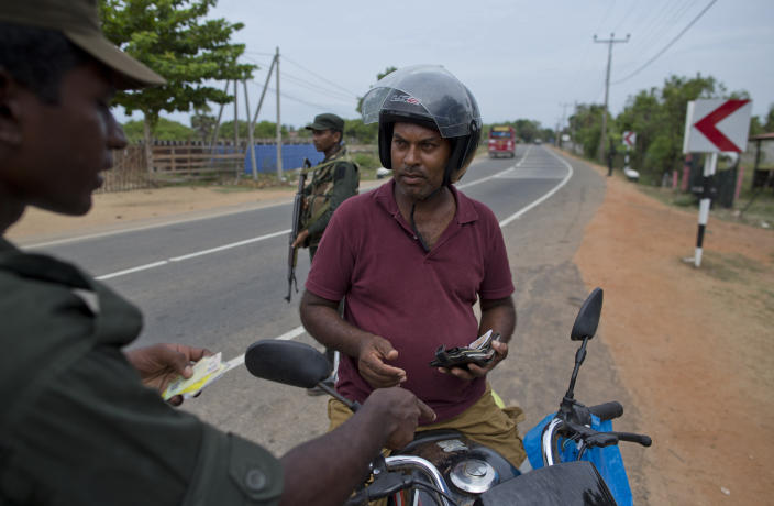 An army officer checks the identity of a man on a motor bike at a roadside checkpoint in Kalmunai, Sri Lanka, Sunday, April 28, 2019. Police in Ampara showed The Associated Press on Sunday the explosives, chemicals and Islamic State flag they recovered from the site of one security force raid in the region as Sri Lanka's Catholics celebrated at televised Mass in the safety of their homes. (AP Photo/Gemunu Amarasinghe)