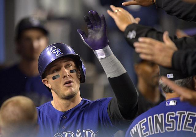 Colorado Rockies' Troy Tulowitzki, left, is congratulated by teammates after scoring on a double by Nolan Arenado during the fourth inning of their baseball game against the Los Angeles Dodgers, Saturday, Sept. 28, 2013, in Los Angeles. (AP Photo/Mark J. Terrill)