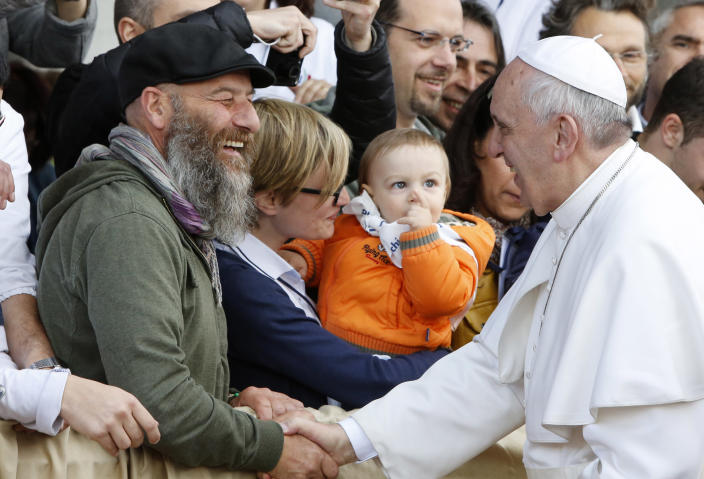 """Pope Francis greets faithful as he arrives at the Don Gnocchi Foundation for assistance to disabled and elderly to celebrate the rite of the washing of the feet, in Rome, Thursday, April 17, 2014. Pope Francis has washed the feet of 12 elderly and disabled people — women and non-Catholics among them — in a pre-Easter ritual designed to show his willingness to serve like a """"slave."""" Francis' decision in 2013 to perform the Holy Thursday ritual on women and Muslim inmates at a juvenile detention center just two weeks after his election helped define his rule-breaking papacy. It riled traditionalist Catholics, who pointed to the Vatican's own regulations that the ritual be performed only on men since Jesus' 12 apostles were men. The 2014 edition brought Francis to a center for the elderly and disabled Thursday. Francis kneeled down, washed, dried and kissed the feet of a dozen people, some in wheelchairs. He said the ritual is a gesture of """"a slave's service."""" (AP Photo/Riccardo De Luca)"""