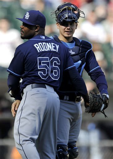 Tampa Bay Rays relief pitcher Fernando Rodney (56) celebrates with catcher Jose Lobaton (59) after defeating the Chicago White Sox 8-3 in a baseball game in Chicago, Sunday, April 28, 2013. (AP Photo/Paul Beaty)