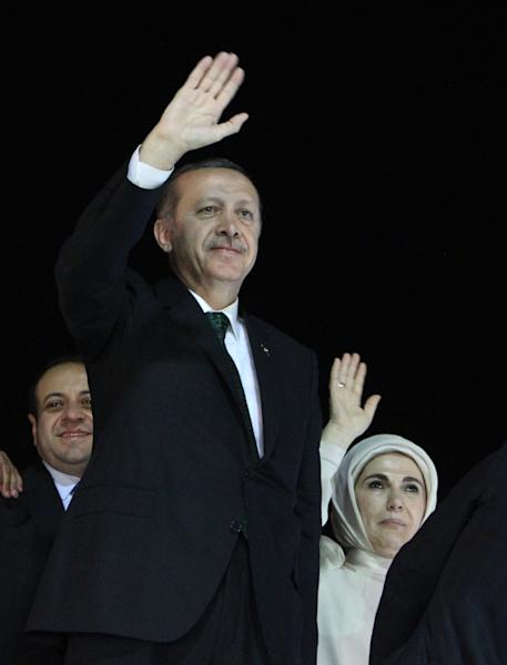 Turkish Prime Minister Recep Tayyip Erdogan and his wife Emine wave to the crowd upon their arrival at the Ataturk Airport of Istanbul early Friday, June 7, 2013. Erdogan took a combative stance on his closely watched return to the country early Friday, telling supporters who thronged to greet him that the protests that have swept the country must come to an end. (AP Photo/Thanassis Stavrakis)
