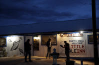 """People stand around the Little A'Le'Inn during an event inspired by the """"Storm Area 51"""" internet hoax, Thursday, Sept. 19, 2019, in Rachel, Nev. Hundreds have arrived in the desert after a Facebook post inviting people to """"see them aliens"""" got widespread attention and gave rise to festivals this week. (AP Photo/John Locher)"""