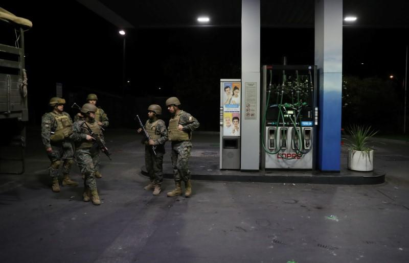 Soldiers stand guard at a gasoline station after Chile's President Sebastian Pinera declaring a state of catastrophe, due to the outbreak of the coronavirus disease (COVID-19), in Santiago, Chile