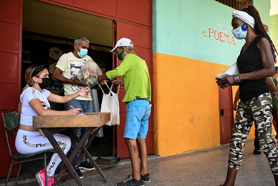 Cubans buy a donation food module at a supermarket in Arroyo Naranjo municipality in Havana, on August 11, 2021. - Cubans receive a free food module with products donated by several countries in an attempt to to alleviate the shortage of food and medicines following the difficult situation caused by Covid-19 in the country. (Photo by YAMIL LAGE / AFP) (Photo by YAMIL LAGE/AFP via Getty Images)