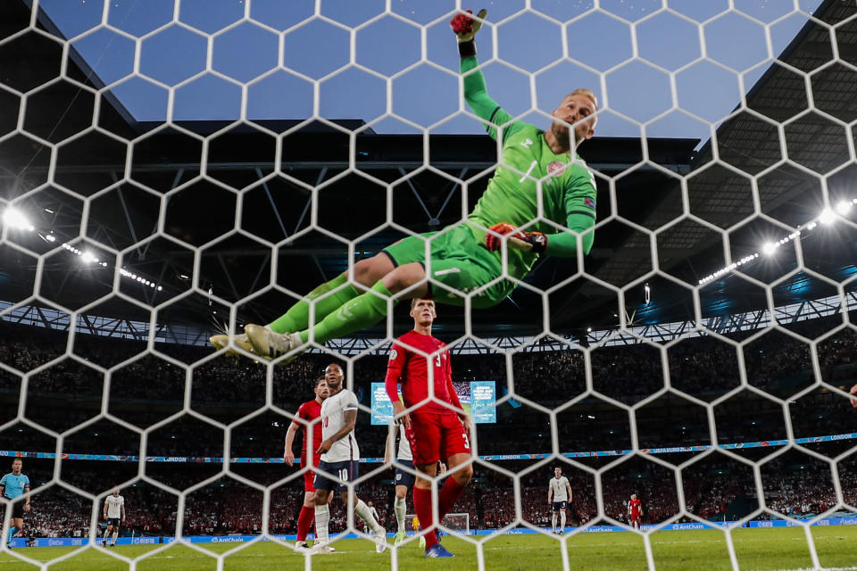 Denmark's goalkeeper Kasper Schmeichel jumps the air after saving a shot during the Euro 2020 Soccer Championship semifinal match between England and Denmark at Wembley Stadium in London, Wednesday, July 7, 2021. (AP Photo/Frank Augstein)