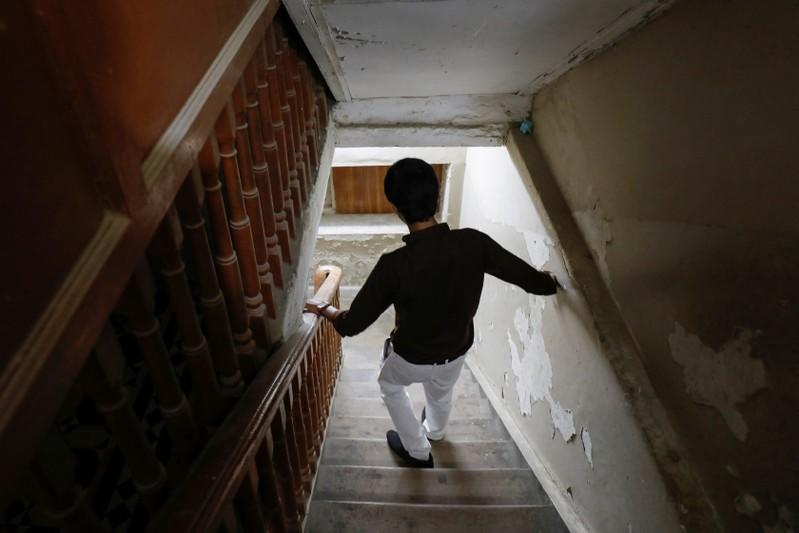 A typhoid fever survivor descends a set of stairs at his family home in Karachi,