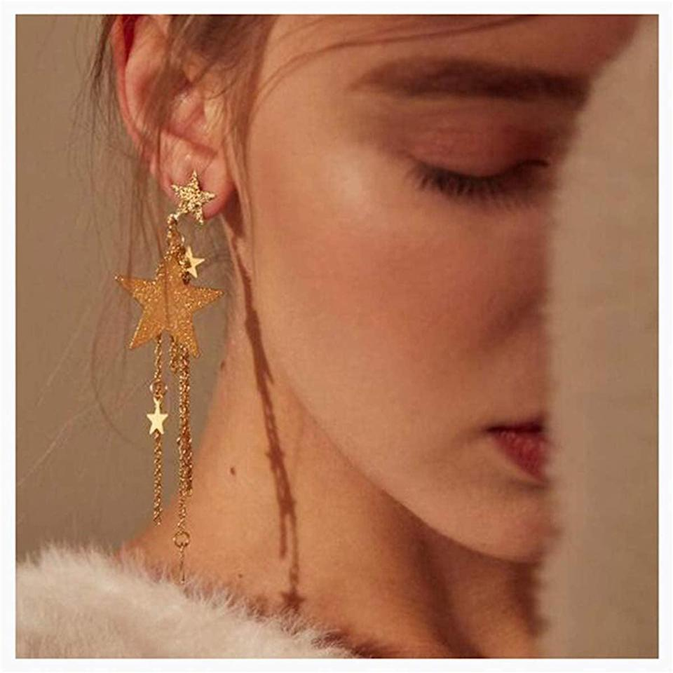 """<p>These <a href=""""https://www.popsugar.com/buy/CanB-Dangle-Star-Earrings-523532?p_name=CanB%20Dangle%20Star%20Earrings&retailer=amazon.com&pid=523532&price=13&evar1=fab%3Aus&evar9=46947746&evar98=https%3A%2F%2Fwww.popsugar.com%2Ffashion%2Fphoto-gallery%2F46947746%2Fimage%2F46949335%2FCanB-Dangle-Star-Earrings&list1=shopping%2Camazon%2Choliday%2Choliday%20fashion%2Cfashion%20shopping&prop13=mobile&pdata=1"""" rel=""""nofollow noopener"""" class=""""link rapid-noclick-resp"""" target=""""_blank"""" data-ylk=""""slk:CanB Dangle Star Earrings"""">CanB Dangle Star Earrings </a> ($13) are the perfect touch to your look.</p>"""
