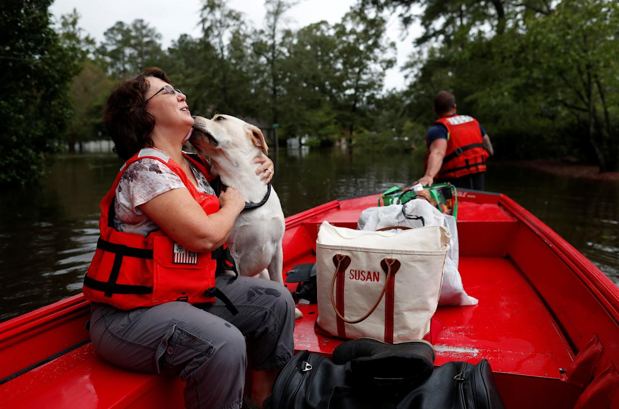 Susan Hedgpeth hugs her dog Cooper, as they go to higher ground via the United States Coast Guard in Lumberton.