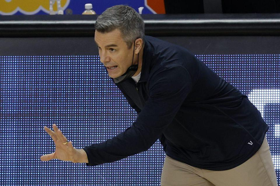 Tony Bennett of the Virginia Cavaliers courtside holding his left hand out