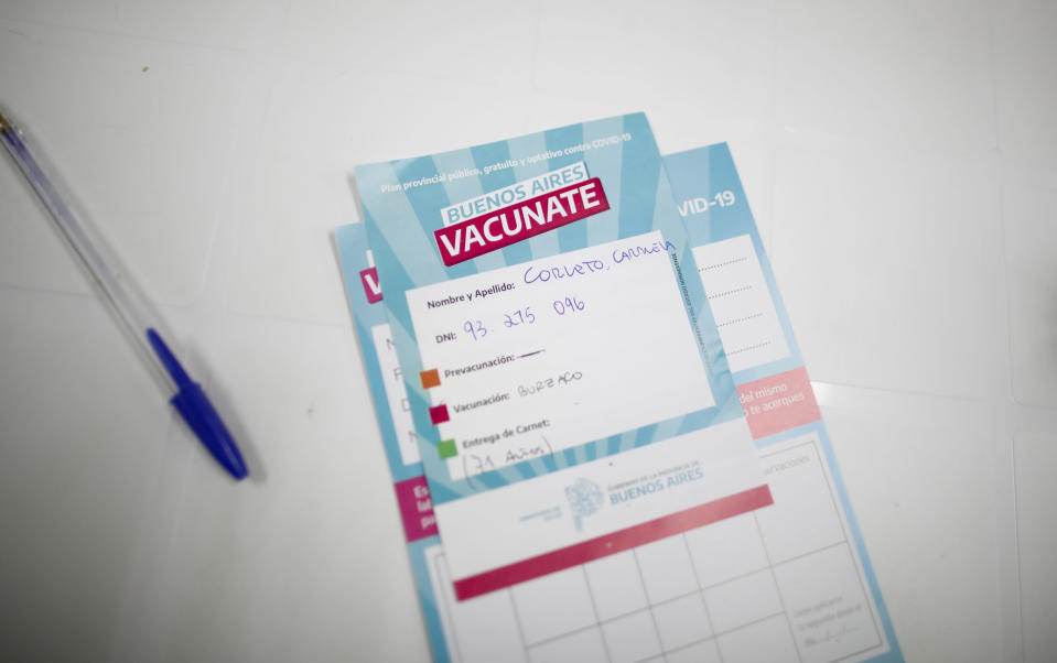 Carmela Corleto's vaccination certificate sits on a table after a nurse administered her first shot of the AstraZeneca vaccine for COVID-19 at a vaccination center in Almirante Brown, Argentina, Friday, April 23, 2021. (AP Photo/Natacha Pisarenko)