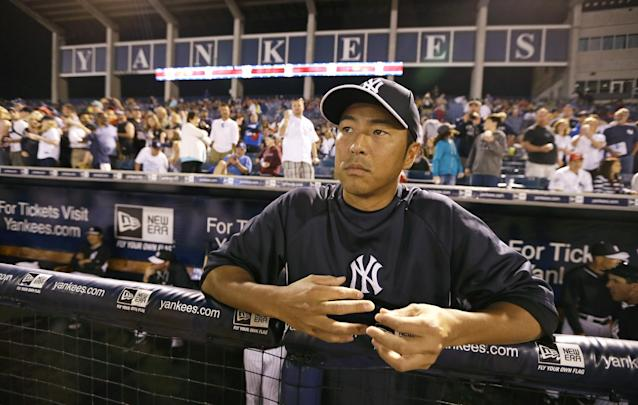 New York Yankees starting pitcher Hiroki Kuroda stands in the dugout before an exhibition baseball game against the Baltimore Orioles Tuesday, March 4, 2014, in Tampa, Fla. (AP Photo/Charlie Neibergall)