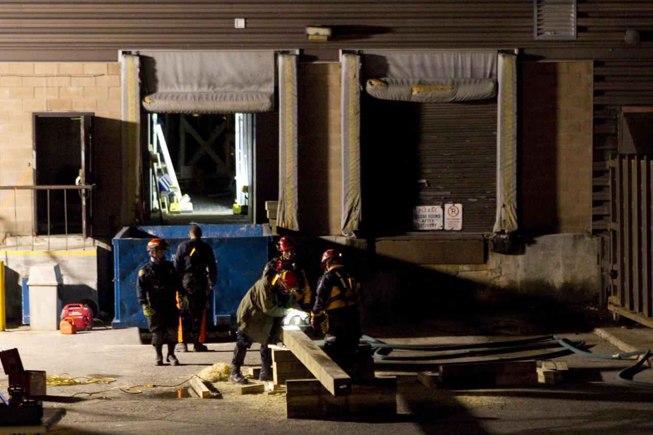 Rescue workers cut timber as attempts continue to secure the building before searching for any survivors at the site of the collapsed roof of the Algo Centre Mall in Elliot Lake, Ontario on Monday June 25, 2012. (AP Photo/The Canadian Press, Chris Young)
