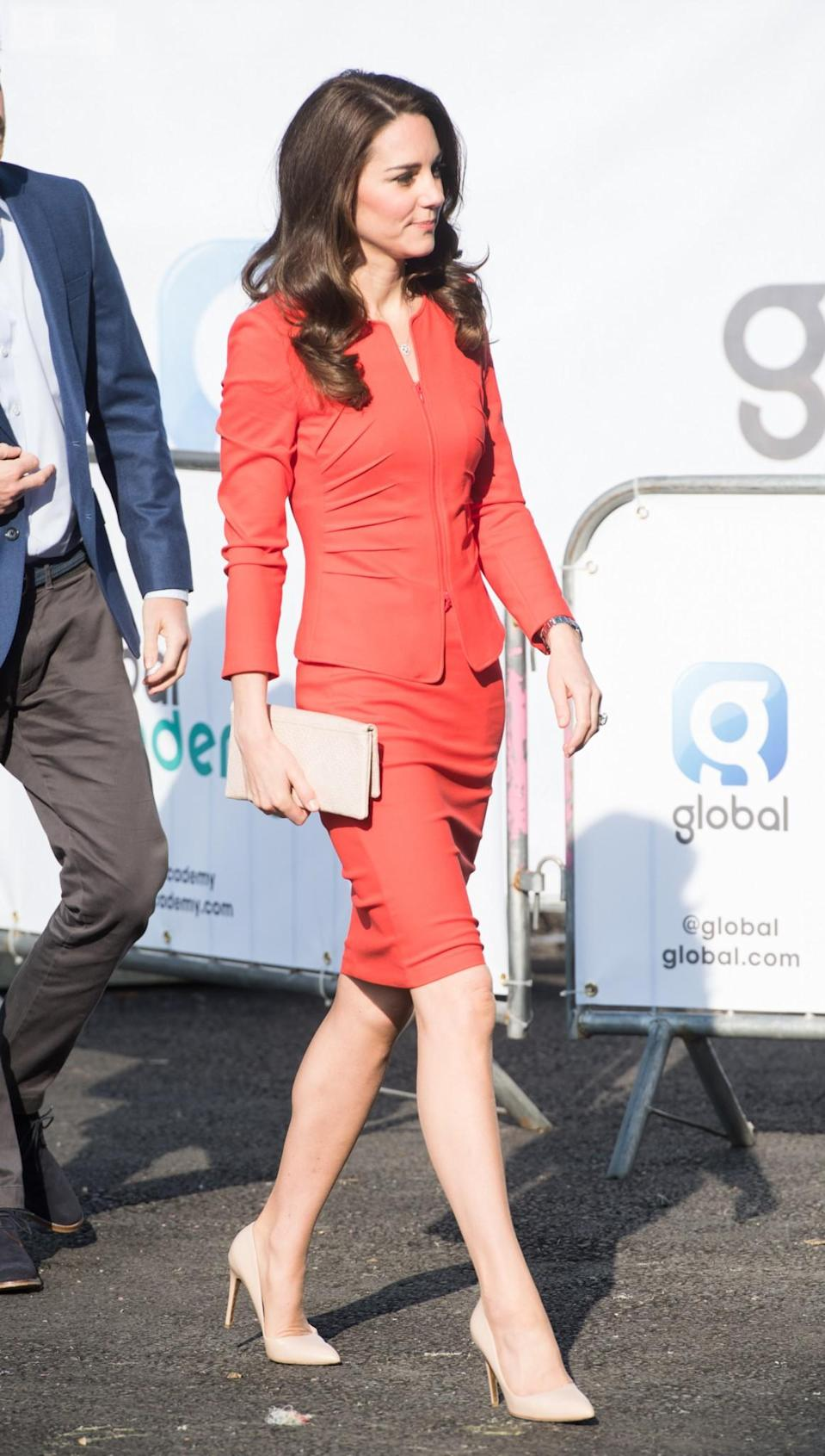 <p>Kate donned a tomato red skirt suit for the opening of The Global Academy. Her workwear look was by Armani Collezioni – the lower-priced line from the Italian brand – and featured a ruched jacket and tight-fitting pencil skirt. As always, the Duchess chose her trusty nude accessories, wearing Rupert Sanderson heels and a clutch by Etui.<br><i>[Photo: PA]</i> </p>