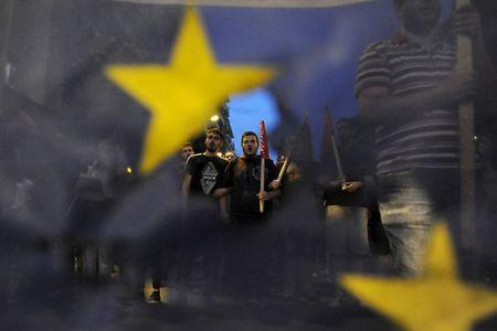 Anti-EU protesters are seen through a burned and torn European Union flag during a protest at the northern city of Thessaloniki, Greece July 1, 2015. REUTERS/Alexandros Avramidis