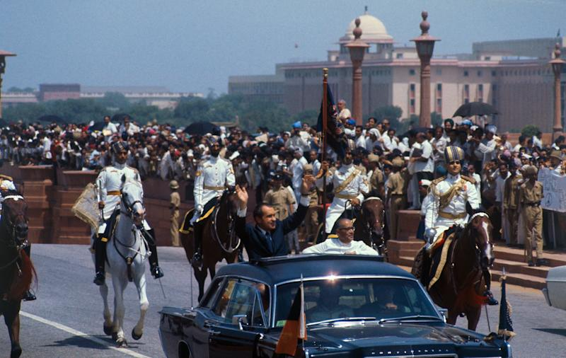 U.S. President Richard Nixon waves to crowds as he rides in open car with the acting president of India, Mohammad Hidyatullah, in motorcade from airport on July 31, 1969. | Bettmann Archive/Getty Images