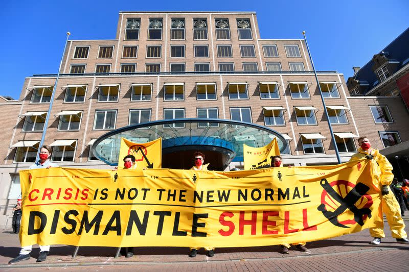 Protesters shout during a demonstration outside of the Shell headquarters, in The Hague