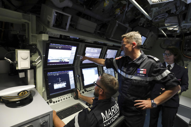 "FILE - In this July 12, 2019 file photo, French navy commander Axel Roch poses in the navigation and operations center in the new nuclear-powered submarine ""Suffren"" in Cherbourg, north-western France. Stealthily cruising the ocean deeps, deliberately hiding from the world now in turmoil, the crews of nuclear-armed submarines may be among the last pockets of people anywhere who are still blissfully unaware of how the coronavirus pandemic is turning life upside down. The new coronavirus causes mild or moderate symptoms for most people, but for some, especially older adults and people with existing health problems, it can cause more severe illness or death. (Ludovic Marin/Pool via AP, File)"