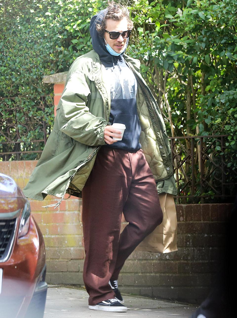<p>Harry Styles keeps his mask close for an outing in London on Monday.</p>