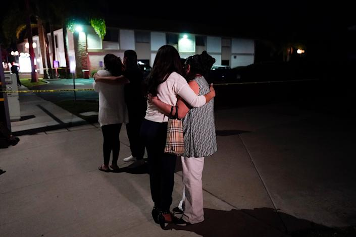 People comfort each other near a business where a shooting occurred in Orange, Calif. Authorities say 4 people, including a child, died during the shooting March 31.