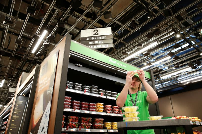 A worker inspects packaged fruit during a tour of an Amazon checkout-free, large format grocery store in Seattle