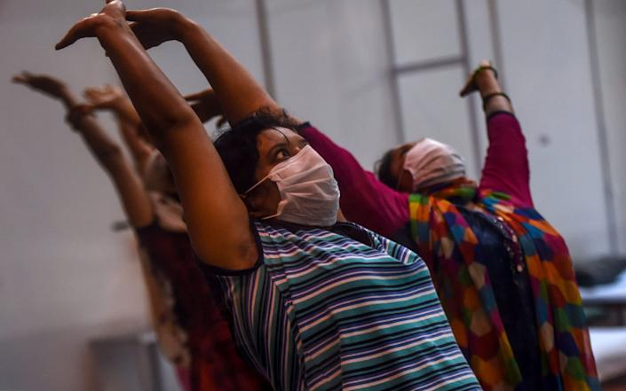 Despite the bleak circumstances, the patients appear to be enjoying unconventional yoga class - AFP