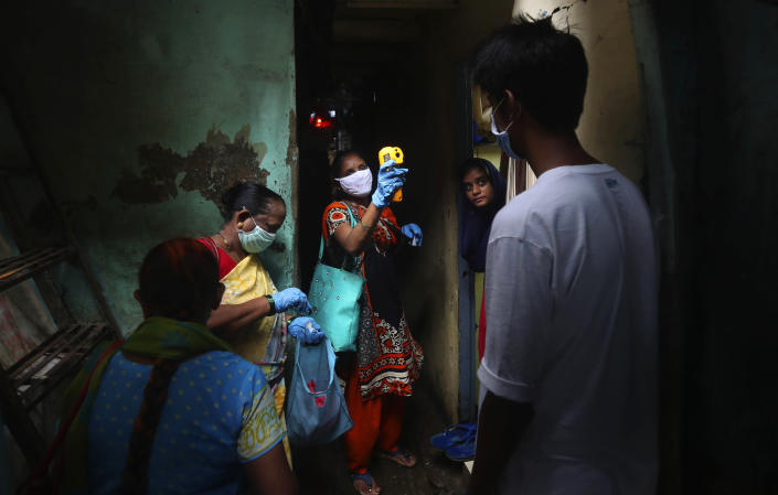 FILE - In this Monday, July 6, 2020, file photo, a health worker screens people for COVID-19 symptoms at Dharavi, one of Asia's biggest slums, in Mumbai, India. In just three weeks, India's confirmed cases shot up from the world's sixth to the third-worst hit country by the coronavirus pandemic, according to a tally by Johns Hopkins University. India's fragile health system was bolstered during stringent monthslong lockdown but could still be overwhelmed by an exponential rise in infections. (AP Photo/Rafiq Maqbool, File)
