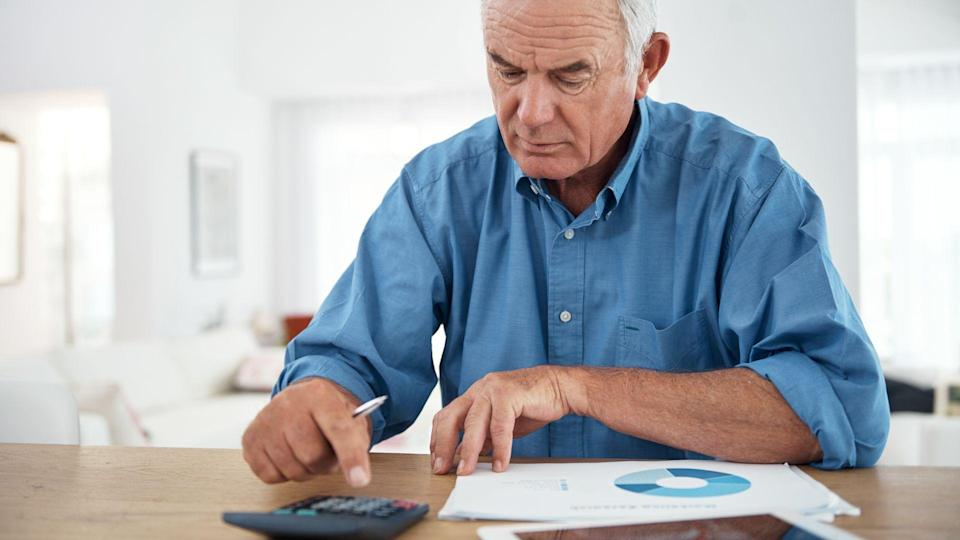 senior man using a calculator while reviewing his budget