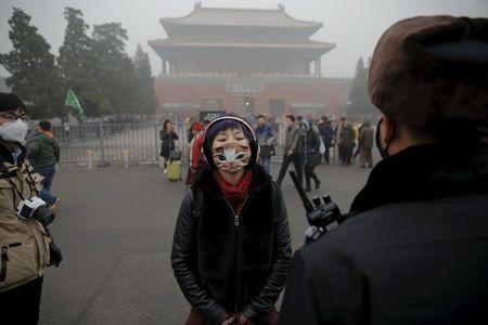 A girl wearing a protective mask talks to a policeman near the Forbidden City on an extremely polluted day as hazardous, choking smog continues to blanket Beijing, China December 1, 2015. REUTERS/Damir Sagolj