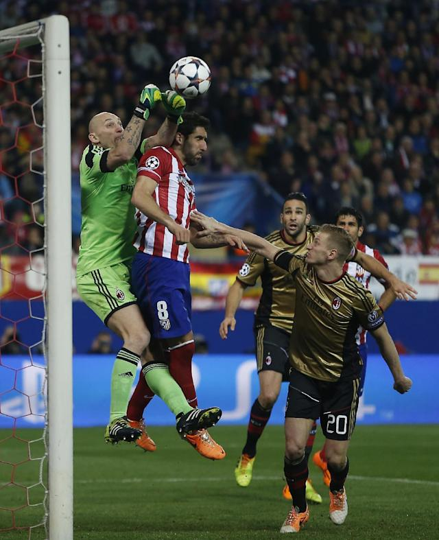 AC Milan goalkeeper Christian Abbiati, left, in action with Atletico's Raul Garcia, second left, during a Champions League last 16 second leg soccer match between Atletico Madrid and AC Milan, at the Vicente Calderon stadium in Madrid, Tuesday, March 11, 2014. (AP Photo/Andres Kudacki)