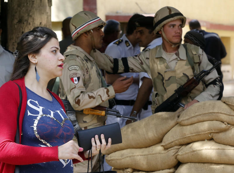 A voter leaves a polling station guarded by soldiers after she casting her ballot on constitutional amendments during the first day of three-day voting in Cairo, Egypt, Saturday, April 20, 2019. Egyptians are voting on constitutional amendments that would allow el-Sissi to stay in power until 2030. (AP Photo/Amr Nabil)