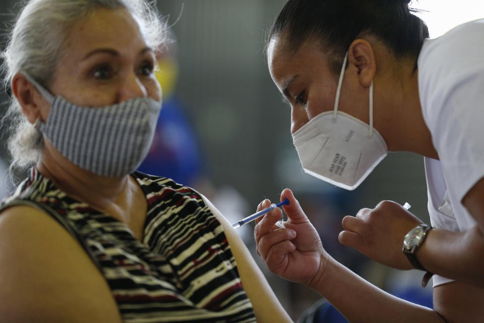 A medical worker injects a woman with a dose of the Russian COVID-19 vaccine Sputnik V at the Palacio de los Deportes, in the Iztacalco borough of Mexico City, Wednesday, Feb. 24, 2021. (AP Photo/Rebecca Blackwell)