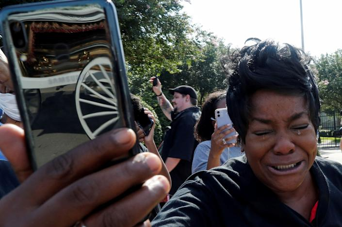 A woman cries as the horse-drawn carriage carrying the casket containing the body of George Floyd, whose death in Minneapolis police custody has sparked nationwide protests against racial inequality, passes by in Pearland, Texas, U.S., June 9, 2020.