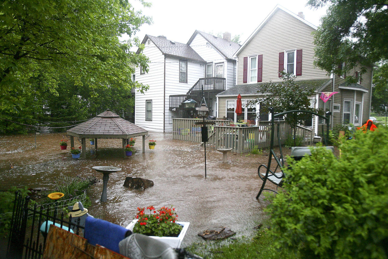 Water flowing from Miller Creek fills the backyards of several homes on West Second Street in Duluth, Minn. after record rainfall hit the area on Wednesday June, 20, 2012. Most areas received seven to 10 inches of rain in the past 24 hours.(AP Photo/The Duluth News-Tribune, Clint Austin)