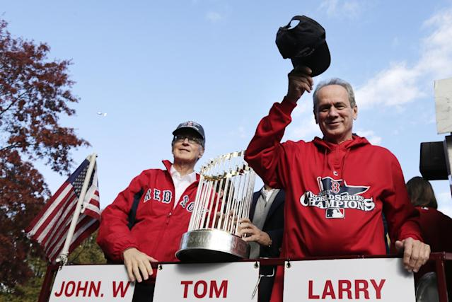 Boston Red Sox president Larry Lucchino, right, tips his cap to fans as majority owner John Henry holds the 2013 World Series championship trophy during a parade in celebration of the baseball team's win, Saturday, Nov. 2, 2013, in Boston. (AP Photo/Charles Krupa)