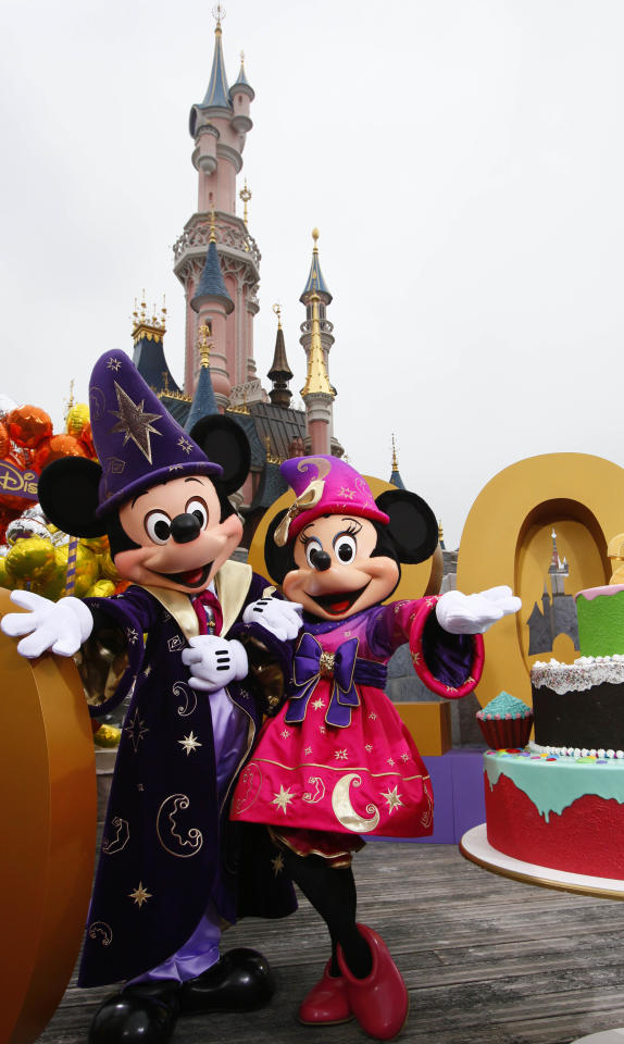 Micky Mouse and Mini Mouse pose for photographers in Disneylands theme park in Marne-la-Vallee, east of Paris, Saturday March 31, 2012. This will mark the 20th year since Disneyland opened in Paris in 1992.(AP Photo/Michel Spingler)
