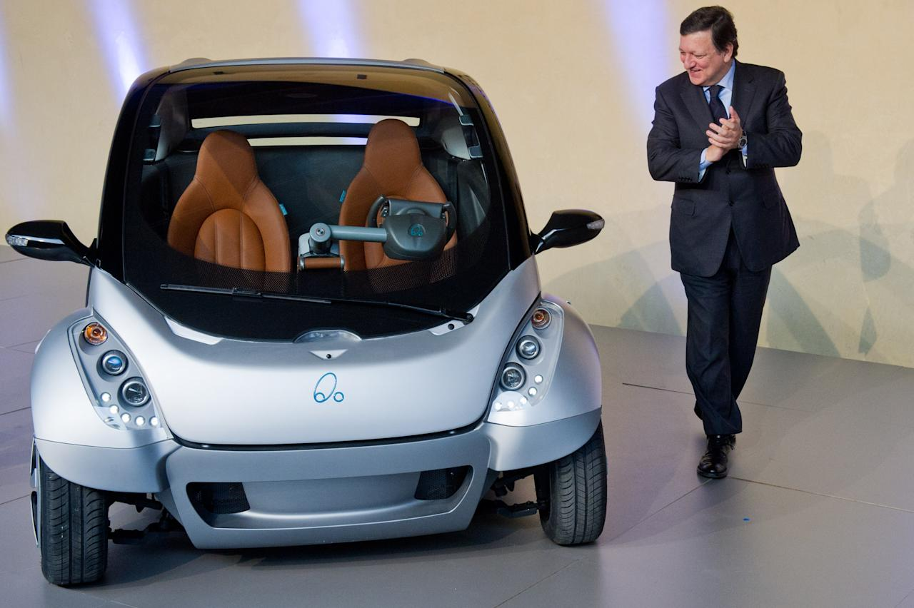 """BRUSSELS, BELGIUM - JANUARY 24:  EU Commission President Jose Manuel Barroso looks at the first prototype of the HIRIKO electric car, during the global launch of Hiriko Driving Mobility at the EU Commssion headquarters on January 24, 2012 in Brussels, Belgium. The electronic eco-friendly vehicle will be manufactured in deprived areas of cities who take up Hiriko's """"social purpose"""" model. Malmo in Sweden has already signed up to trial Hiriko with Berlin, Barcelona, Vitoria-Gasteiz (the second largest Basque city), San Francisco, and Hong Kong expected to follow suit.  (Photo by Geert Vanden Wijngaert/Getty Images)"""