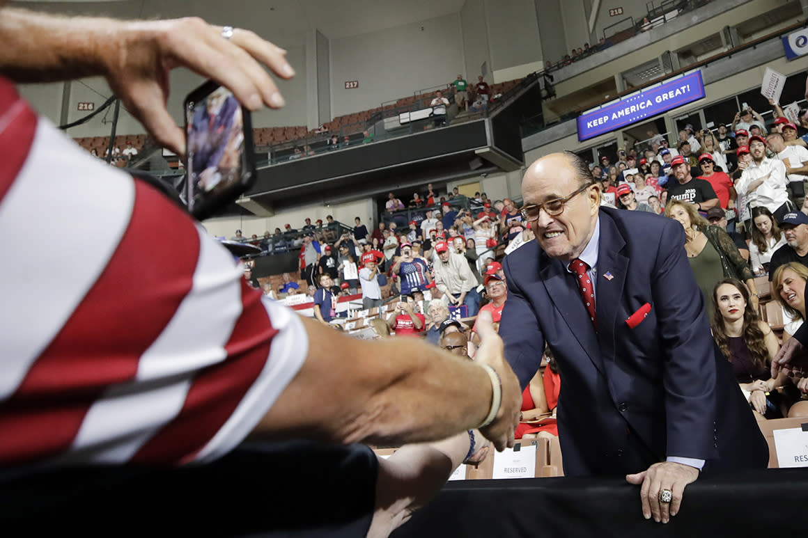Former New York City Mayor Rudy Giuliani shakes a hand as he arrives to President Donald Trump's campaign rally, Thursday, Aug. 15, 2019, in Manchester, N.H. (AP Photo/Elise Amendola)