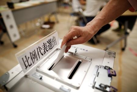 A voter casts a ballot at a voting station during Japan's upper house election in Tokyo