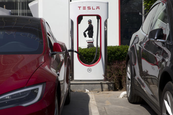 FILE - In this April 14, 2017, file photo, a security guard moves past Tesla electric vehicle charging station in Beijing. More than 200 manufacturers, including Tesla, Volkswagen, BMW, Daimler, Ford, General Motors, Nissan, Mitsubishi and U.S.-listed electric vehicle start-up NIO, transmit position information and dozens of other data points to government-backed monitoring centers, The Associated Press has found. Generally, it happens without car owners' knowledge. (AP Photo/Ng Han Guan, File)