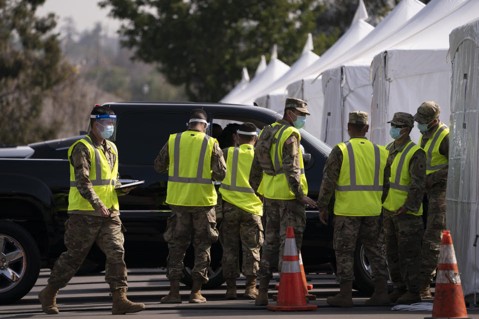 Members of the National Guard work at a joint state and federal COVID-19 vaccination site set up on the campus of California State University of Los Angeles in Los Angeles, Tuesday, Feb. 16, 2021. (AP Photo/Jae C. Hong)