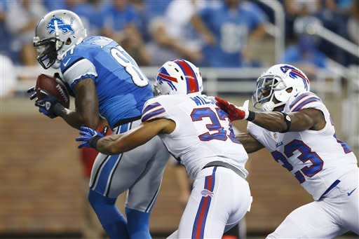 Detroit Lions wide receiver Calvin Johnson (81) makes a touchdown reception as Buffalo Bills strong safety George Wilson (37) and cornerback Aaron Williams (23) defend during the first quarter of an NFL preseason football game in Detroit, Thursday, Aug. 30, 2012. (AP Photo/Rick Osentoski)