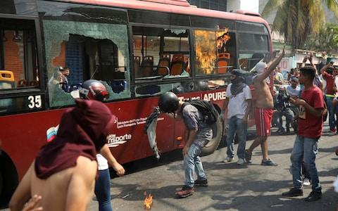 Demonstrators destroying a city bus in Urena - Credit: AP