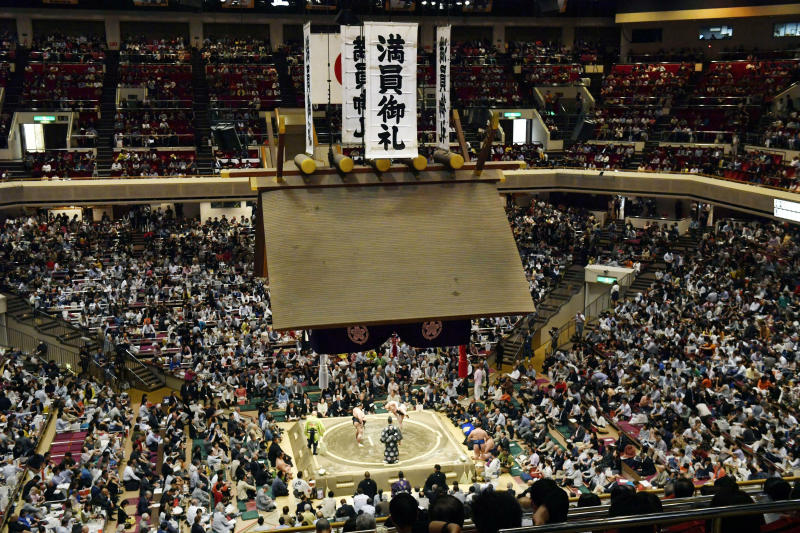 FILE - In this May 12, 2019, file photo, banners thanking for a sellout crowd are displayed on the first day of Summer Grand Sumo Tournament in Tokyo. On Sunday, national broadcaster NHK reported that officials of the Japan Sumo Associating decided to hold the March 8-22 spring grand sumo tournament in Osaka with no spectators. (Yoshitaka Sugawara/Kyodo News via AP, File)